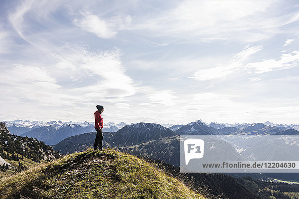 Austria  Tyrol  young woman standing in mountainscape looking at view