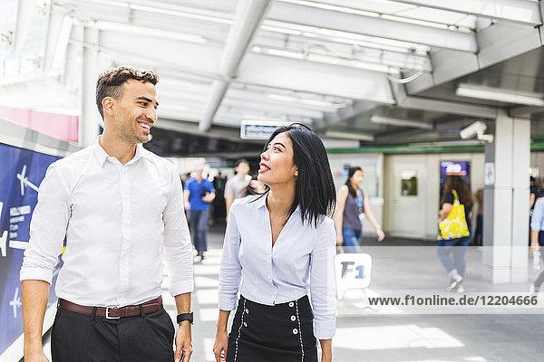 Thailand  Bangkok  lächelnder Geschäftsmann und Geschäftsfrau unterwegs in der Stadt