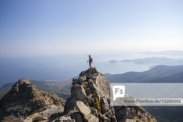 Hiker admires the sea from the top of Monte Capanne  Elba Island  Livorno Province  Tuscany  Italy  Europe