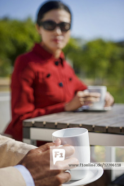 Couple drinking coffee outdoors