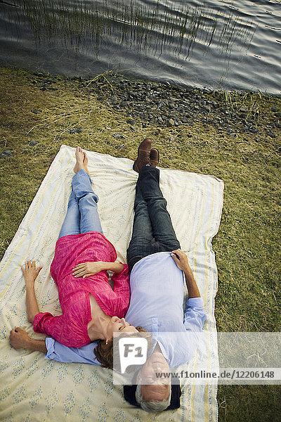 Couple relaxing on blanket near lake