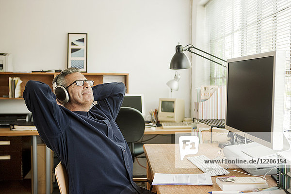 Hispanic businessman relaxing at desk and listening to headphones
