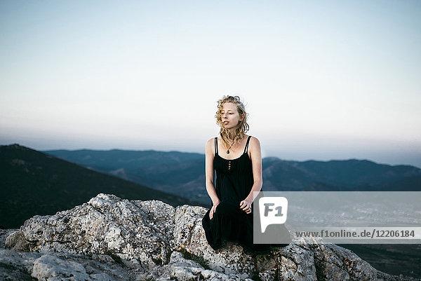 Caucasian woman sitting on rock near mountains