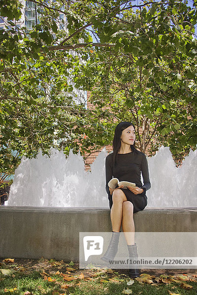 Asian woman sitting outdoors on concrete wall reading book