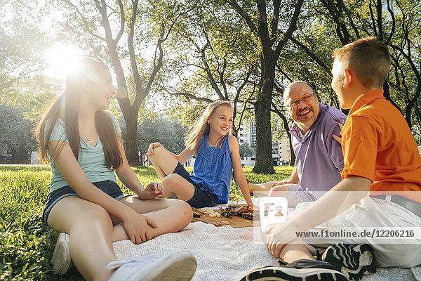 Smiling Caucasian family eating food at picnic