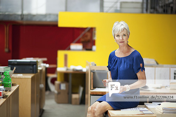 Portrait of serious Caucasian businesswoman sitting on desk