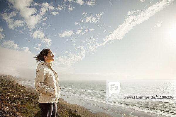 Mixed Race woman standing on beach admiring ocean