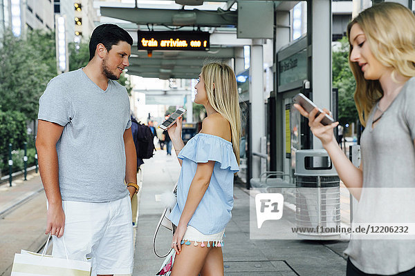 Caucasian woman showing cell phone to man at train station