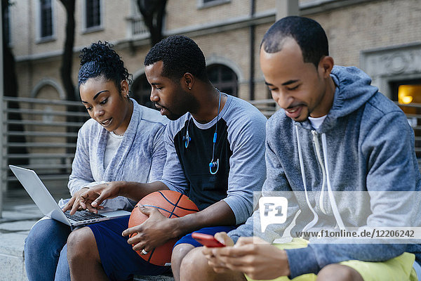 Black friends using laptop and cell phone