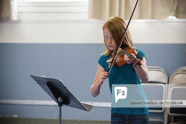 Caucasian girl practicing violin