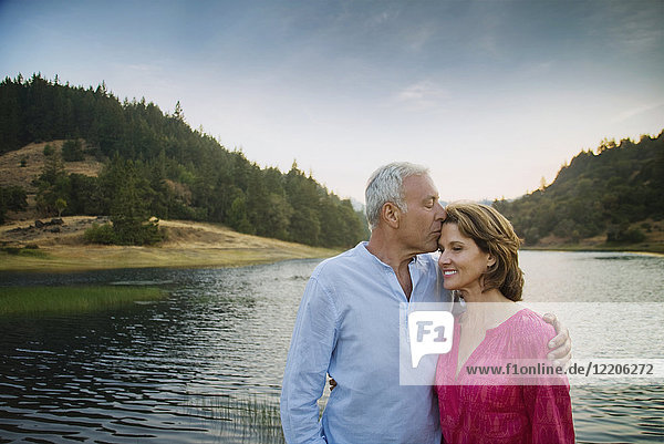 Man kissing woman on forehead near lake