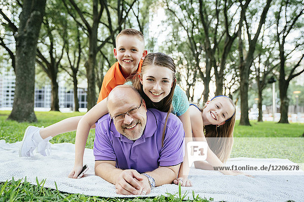 Portrait of Caucasian boy and girls laying on back of father in park