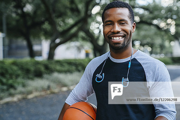 Portrait of smiling Black man holding basketball