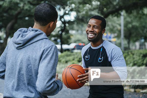 Smiling Black men playing basketball
