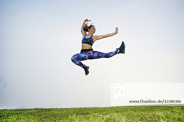 Mixed race woman exercising and jumping in field