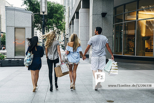 Friends carrying shopping bags in city