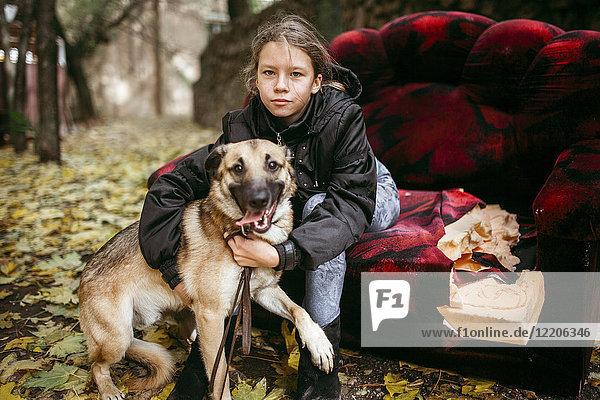 Caucasian woman sitting on sofa outdoors hugging dog