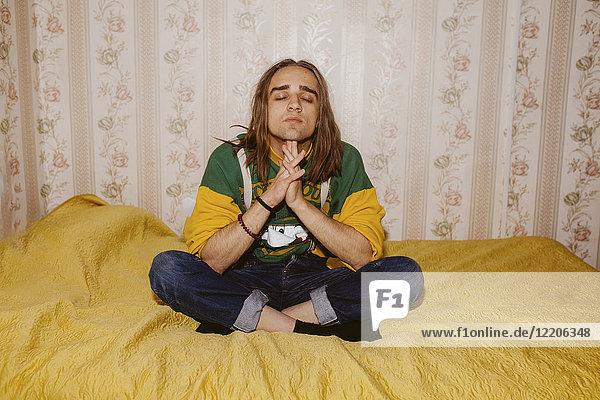 Pensive Caucasian man meditating on bed