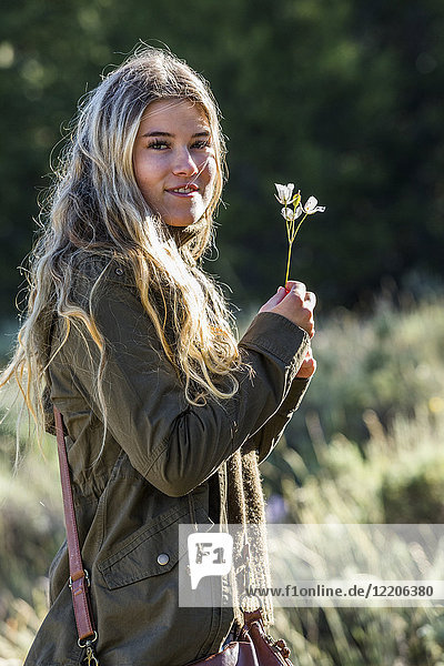 Portrait of smiling Caucasian girl holding wildflower