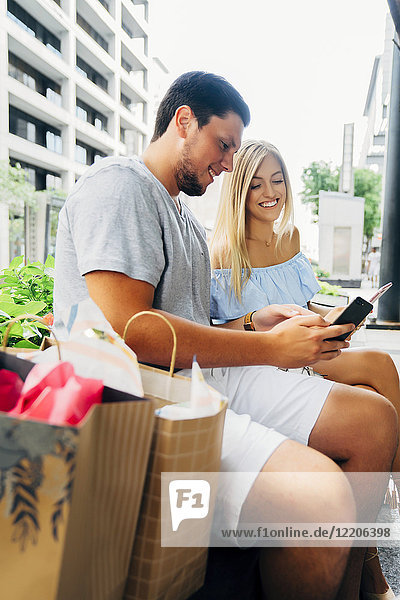 Caucasian couple with shopping bags texting on cell phones