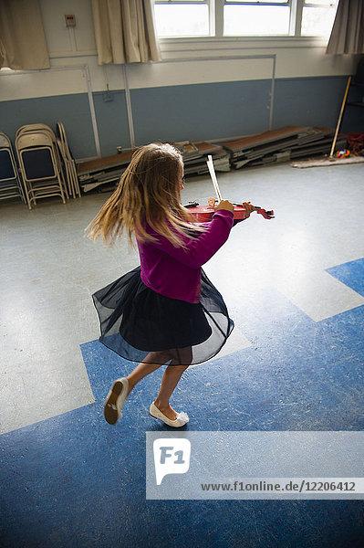 Caucasian girl practicing violin and dancing