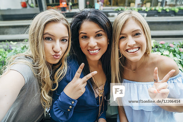 Smiling women posing and gesturing for cell phone selfie