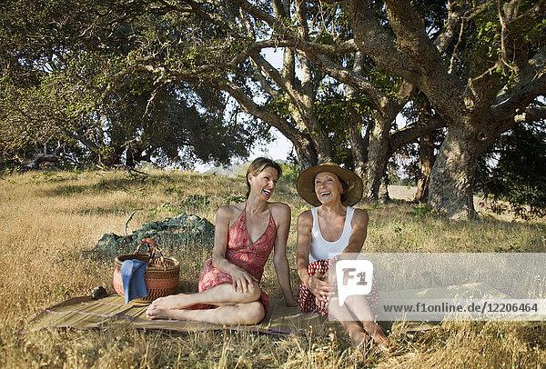 Laughing women relaxing on picnic blanket