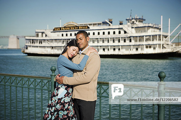 Couple hugging at waterfront near boat
