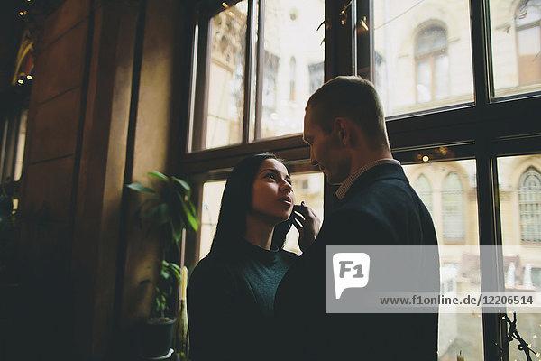 Caucasian couple embracing near window