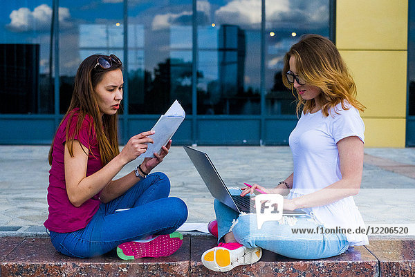 Caucasian women reading paperwork and using laptop outdoors
