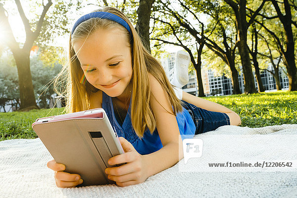 Smiling Caucasian girl laying on blanket in park reading digital tablet