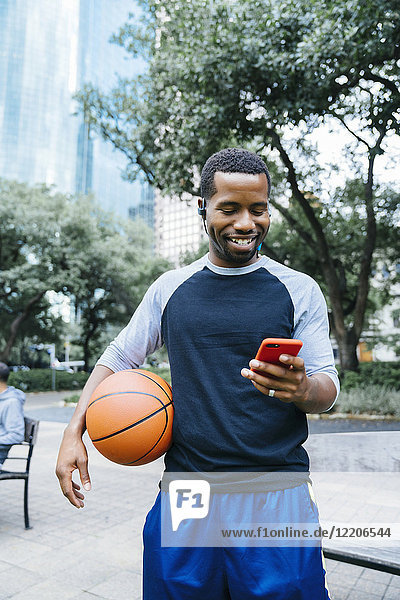 Portrait of Black man listening to earbuds and holding basketball