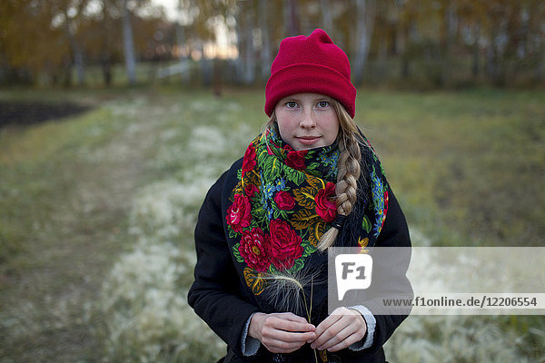 Portrait of Caucasian woman wearing scarf and stocking-cap holding hay seed