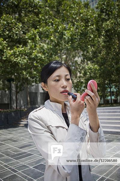 Asian woman applying lipstick outdoors