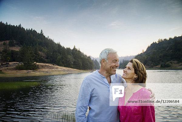 Smiling couple standing near lake