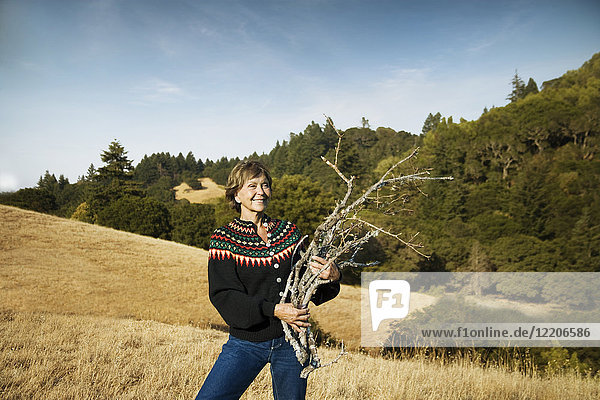 Smiling Caucasian woman gathering branches