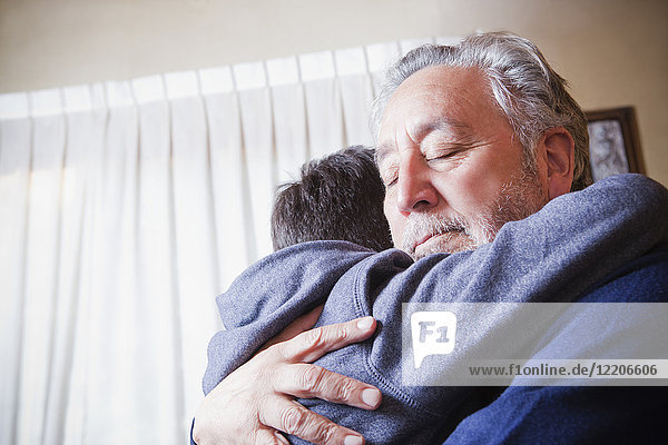 Hispanic grandfather hugging grandson