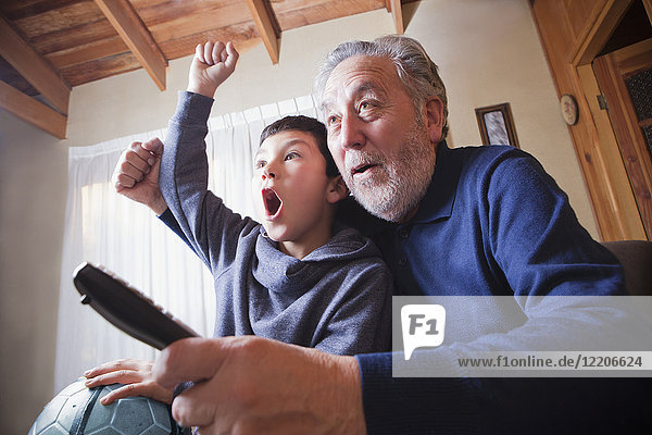 Hispanic grandfather and grandson cheering for soccer game on television