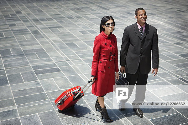 Business people with briefcase and rolling suitcase