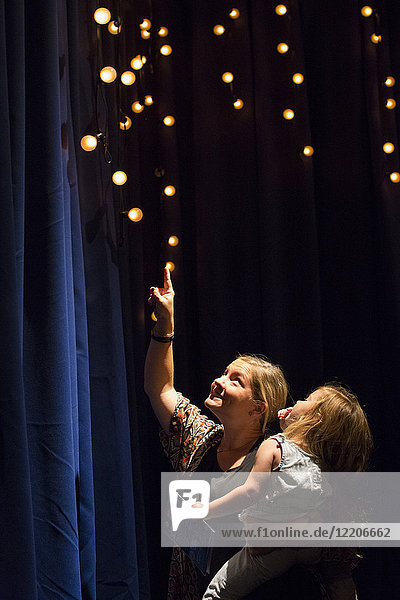 Caucasian mother and daughter looking up at blue curtain