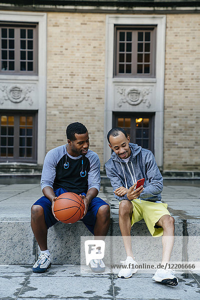 Black men sitting on concrete with basketball and texting on cell phone