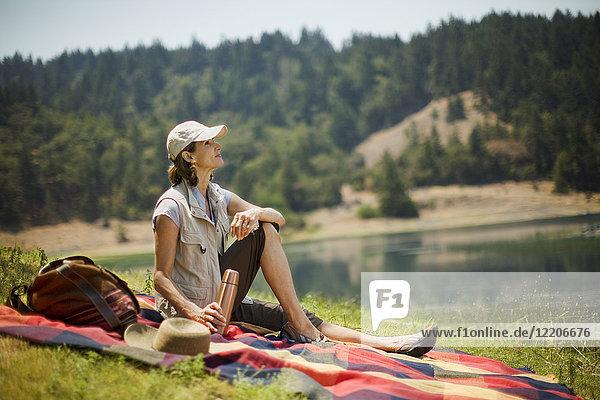 Hispanic woman sitting on picnic blanket near lake