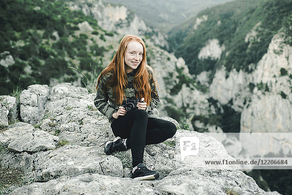 Portrait of smiling Caucasian woman sitting on rock holding camera