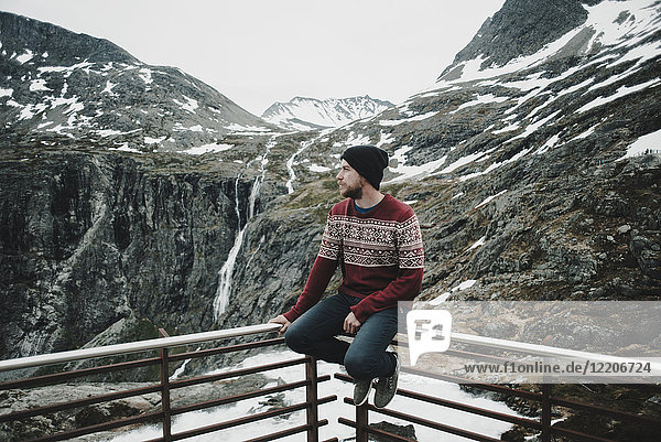 Caucasian man sitting on balcony railing admiring snow on mountain, Caucasian man sitting on balcony railing admiring snow on mountain