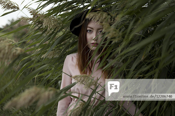 Portrait of serious Asian woman standing in field of tall grass