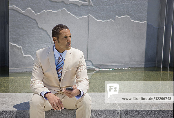 Mixed race businessman sitting outdoors texting on cell phone