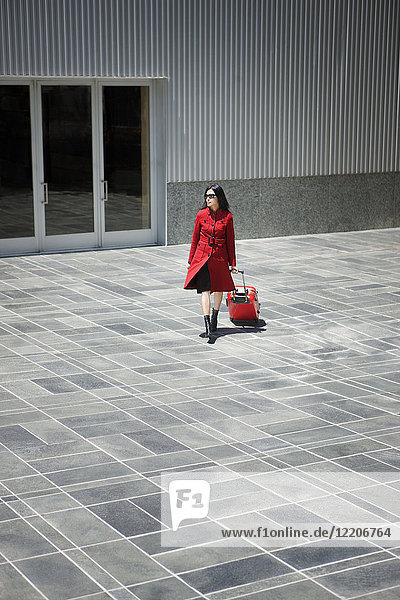 Asian woman pulling rolling suitcase near building