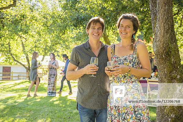 Portrait of smiling Caucasian couple drinking wine outdoors