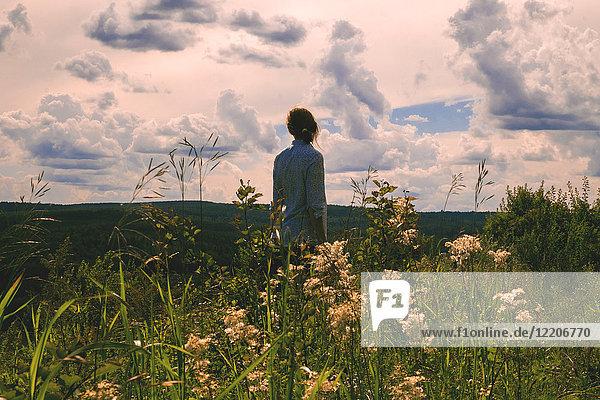 Woman standing in field of wildflowers