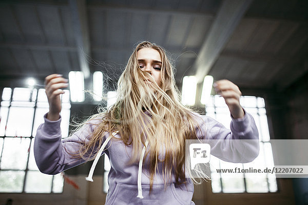 Caucasian woman jumping in gymnasium